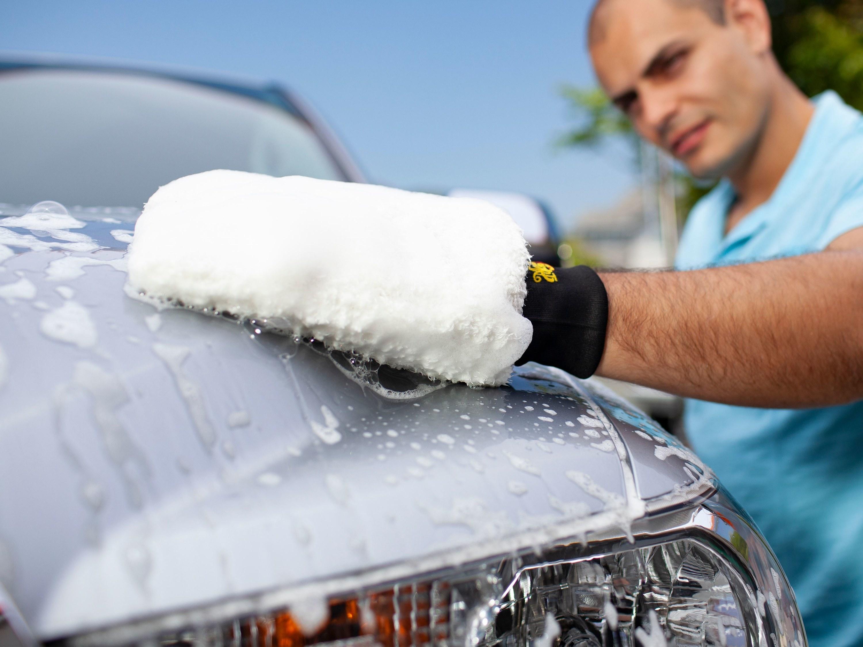 person using mitt to wash their car