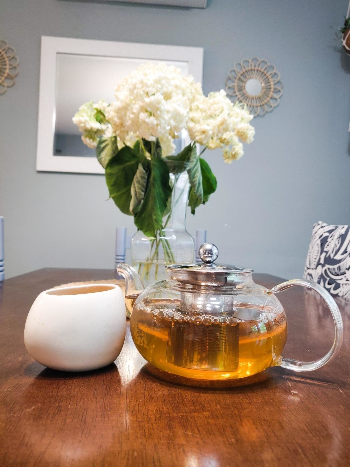 A reviewer showing the glass teapot with tea inside