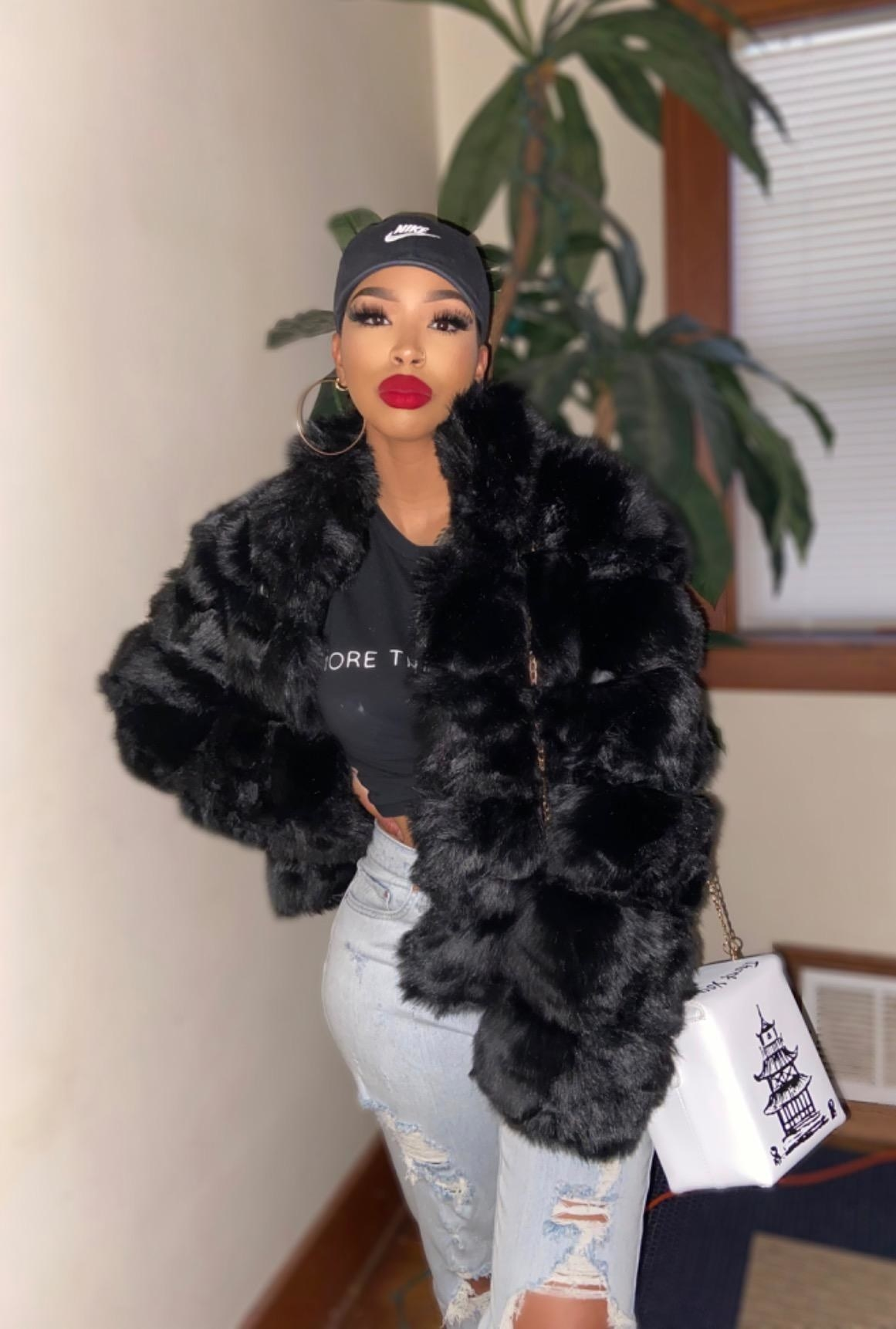 Reviewer wearing the faux fur coat in black
