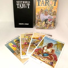 the next world tarot book and box with four cards splayed out