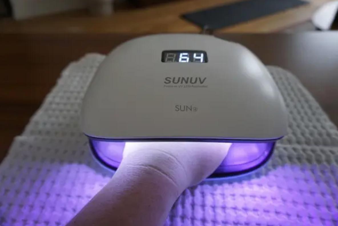 Hand in UV LED gel nail lamp