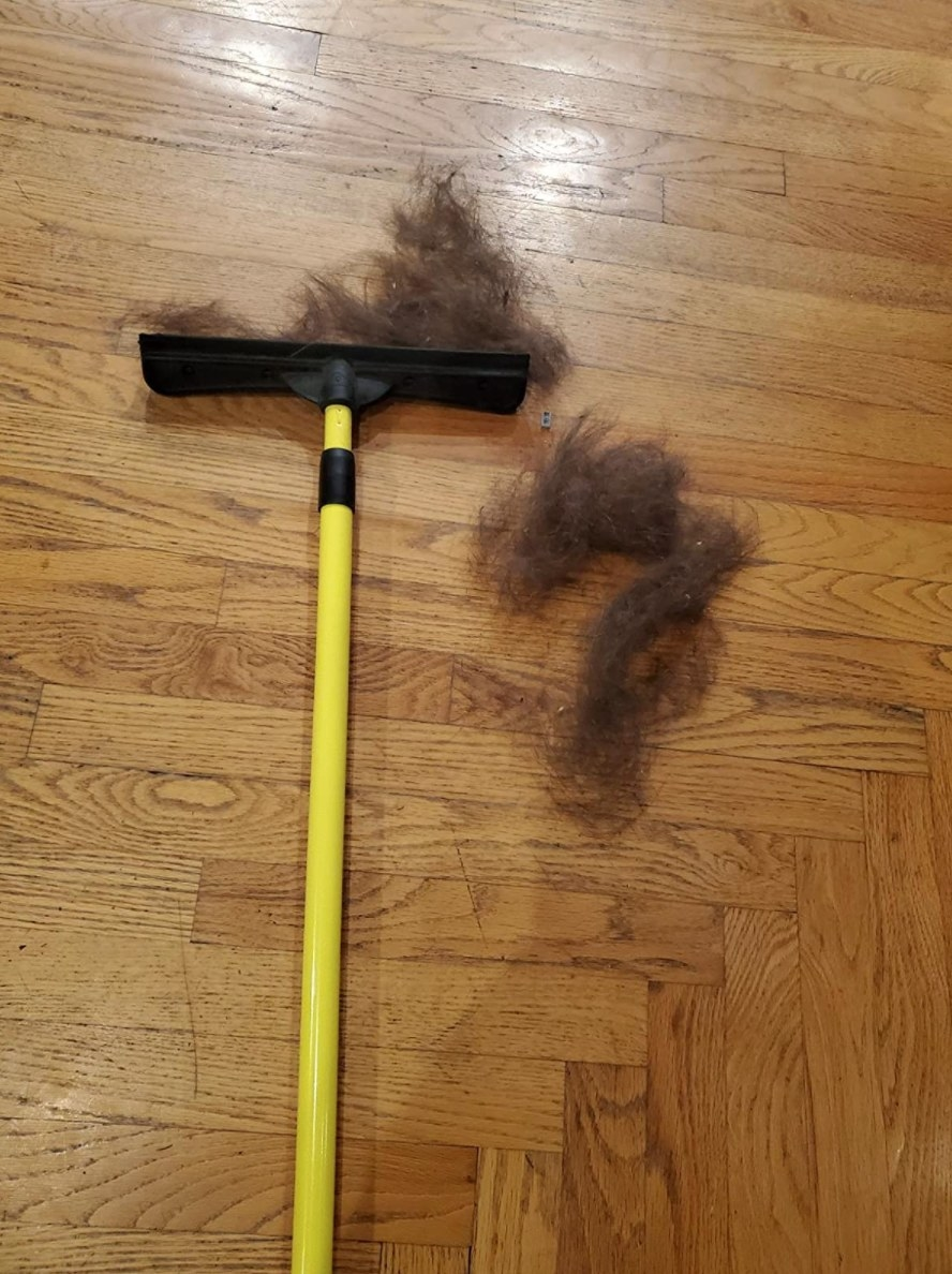 The pet removal brush in yellow with clumps of pet hair