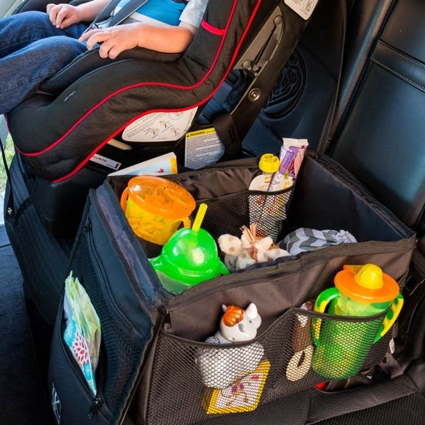black back seat organizer with lots of little kid essentials in it