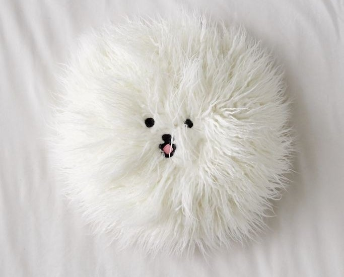 Round faux fur pillow with dog face in center