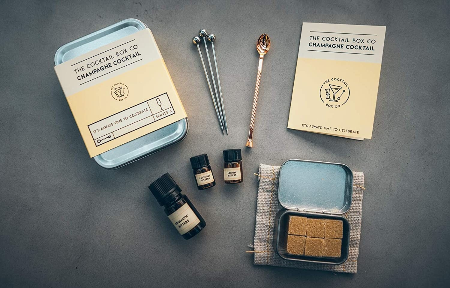 cocktail kit with brown sugar cubes, bitters, a coaster, and stirring spoons.