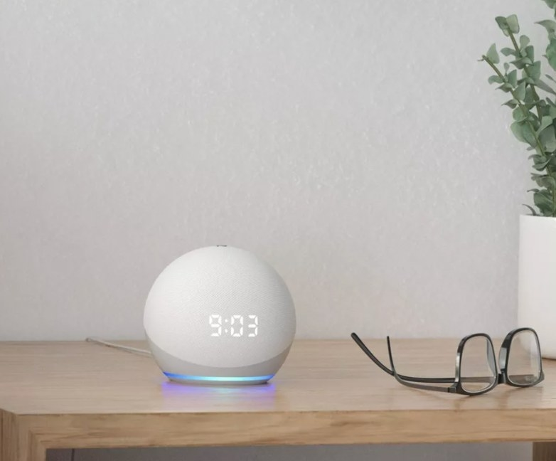 The Smart Hub in white next to a pair of glasses on a bedside table
