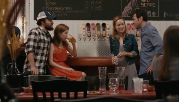 Wilde and Kendrick drink beers in a scene from the movie