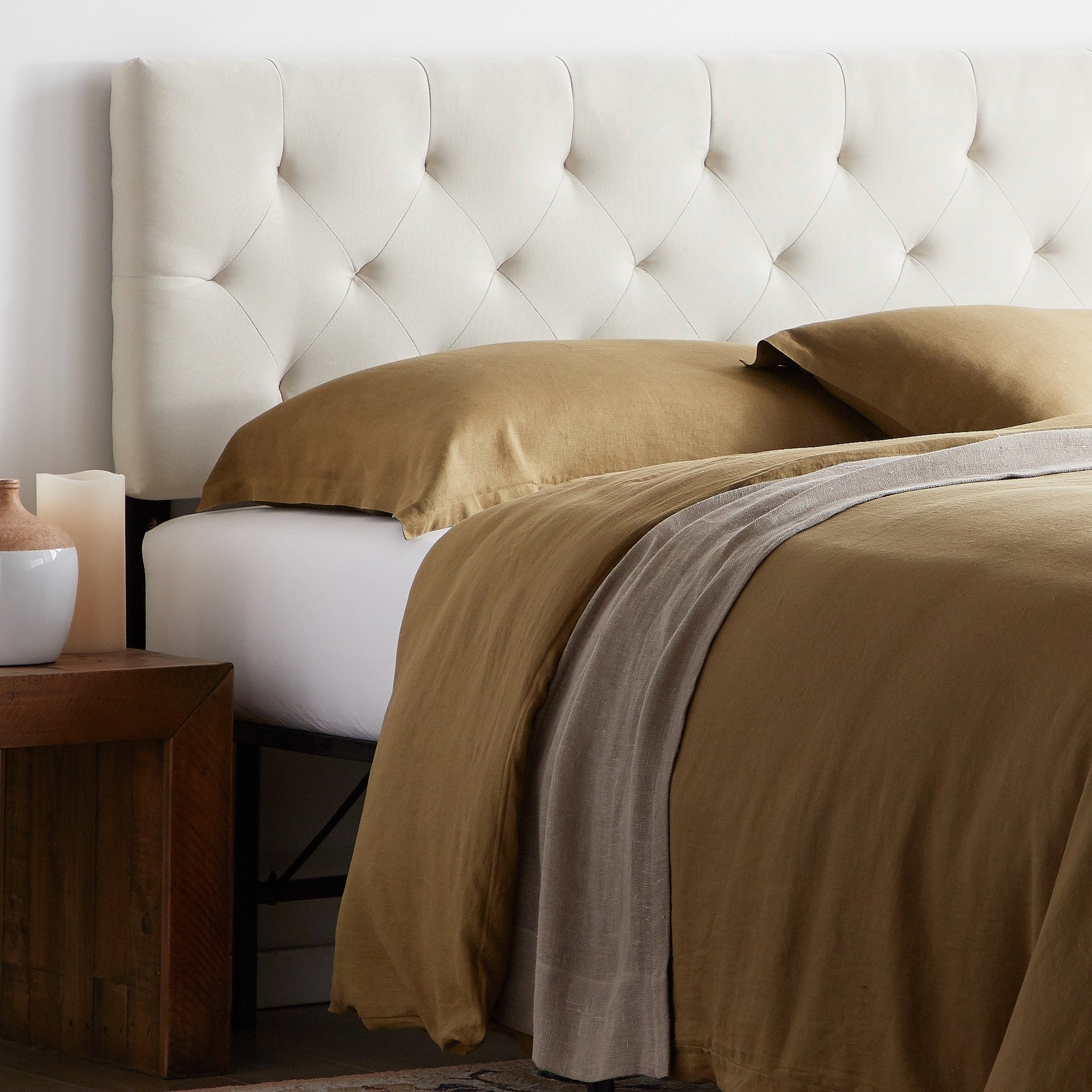 The cream tufted headboard behind a bed