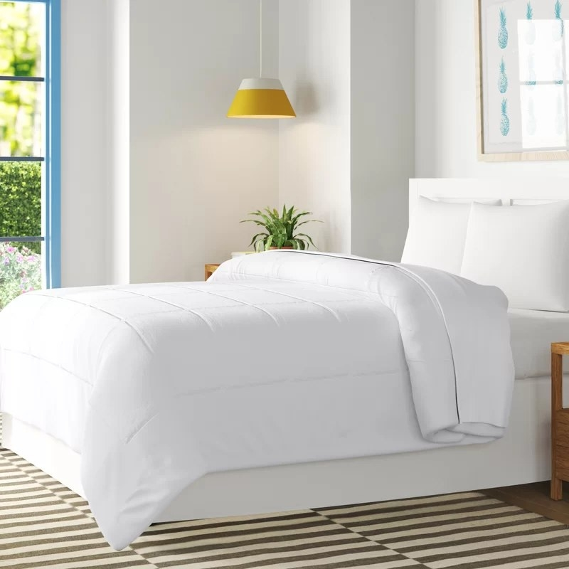 The comforter in white on a queen-sized bed