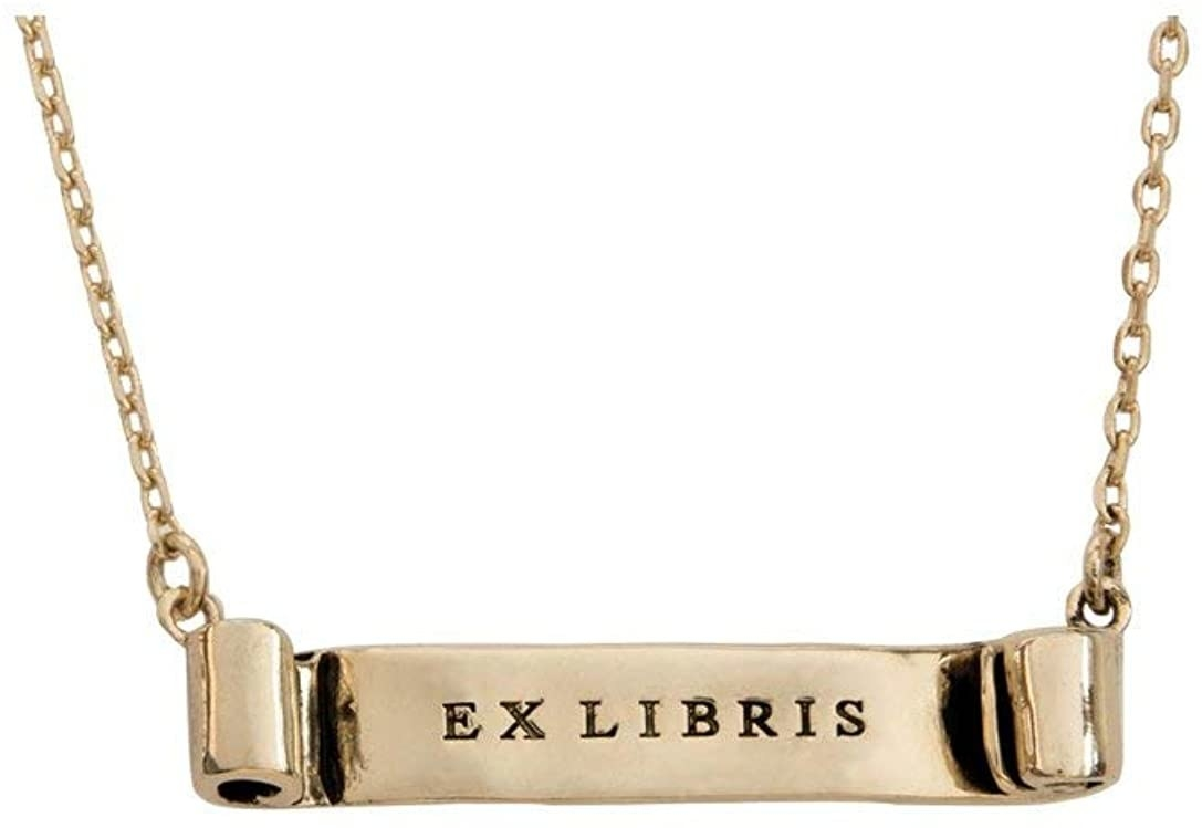 """The gold tone necklace with a scroll that says """"ex libris"""" on it"""