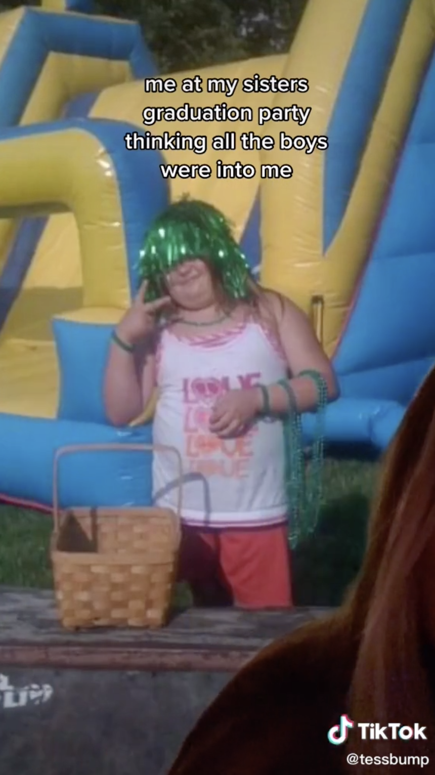"@tessbump wearing a tinsel wig, beads around her wrist, a tank top that says ""Love, Love, Love, Love"" and throwing up the peace sign"
