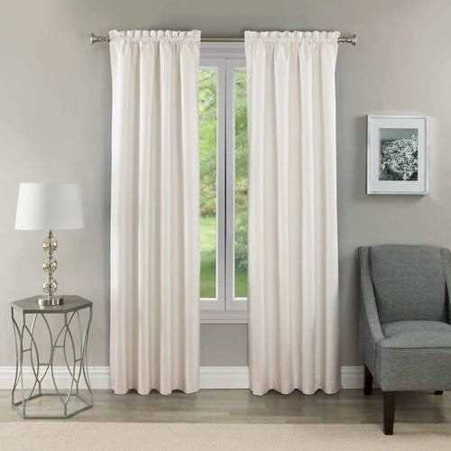 blackout curtains in the color white displayed on a window next to a chair and lamp