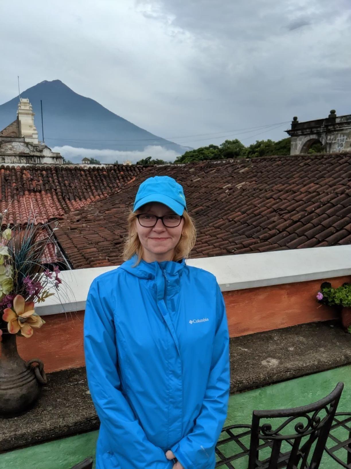 Reviewer wears blue waterproof rain jacket while enjoying a mountain view