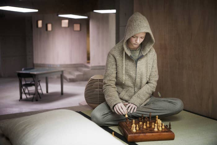 Anya as Morgan sitting on a bed in a hoodie and looking at a chess set