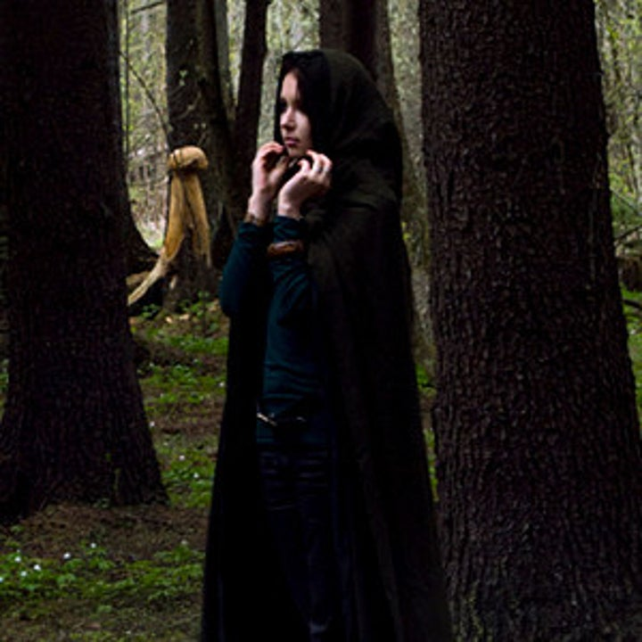 a model wears the black cloak in the forest