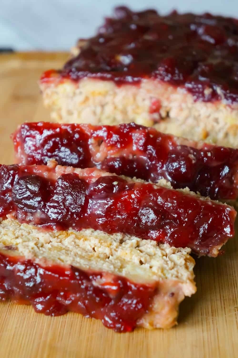 A loaf of turkey meatloaf with cranberry sauce cut into slices.