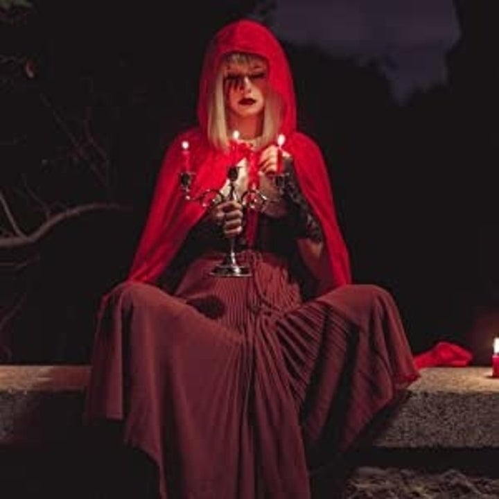 a witchy model wears the red cloak