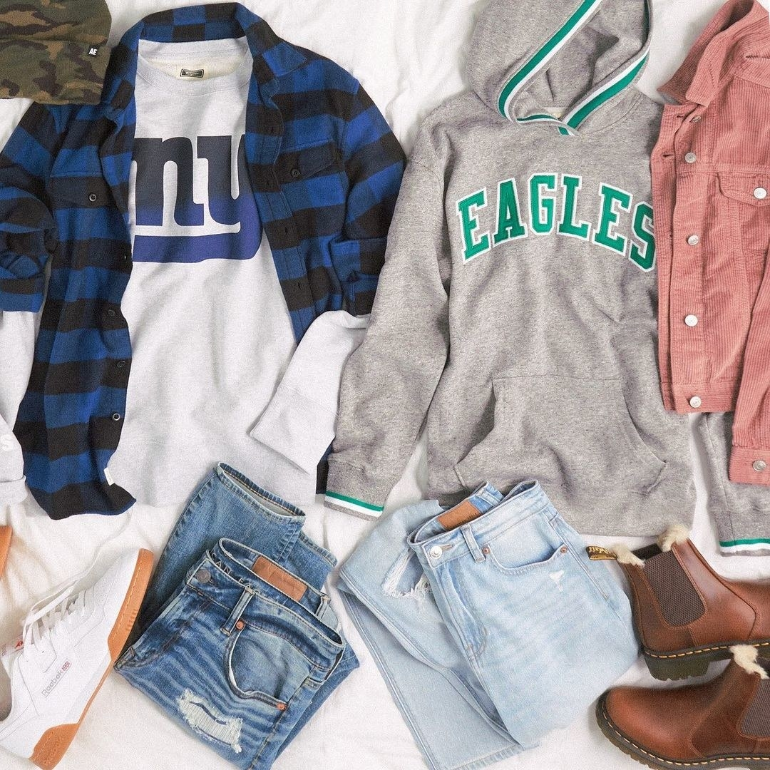 a flat lay of clothing including a new york giants tee and an eagles sweatshirt