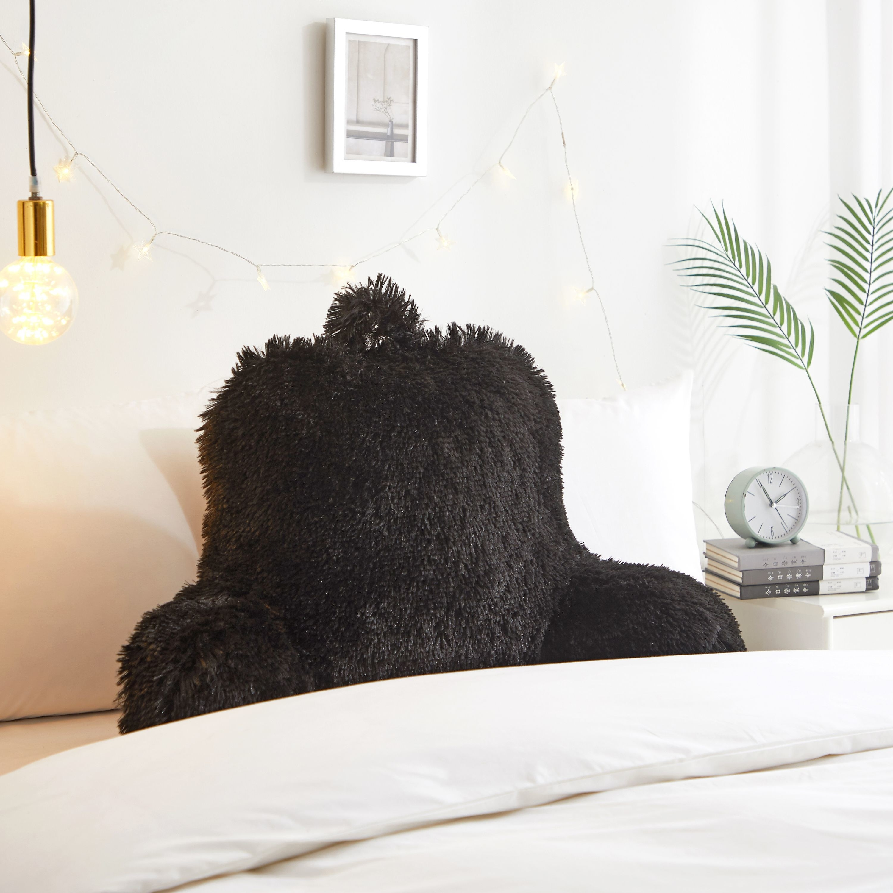 the black faux-fur backrest pillow displayed in a bedroom setting