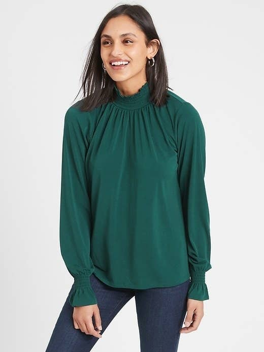 A model wearing the smock necked shirt in green