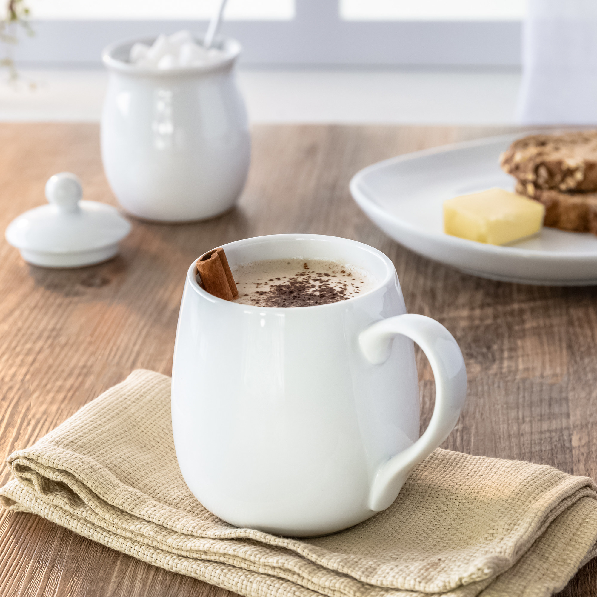 a white porcelain mug displayed on a table with hot cocoa inside of it