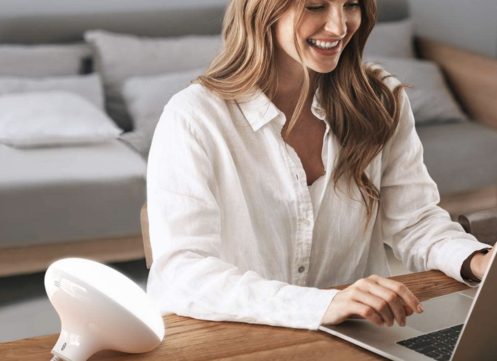 A model sitting next to a round white light therapy lamp propped on a desk