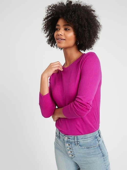 A model wearing the crew-neck sweater in blazing sunset which looks like magenta