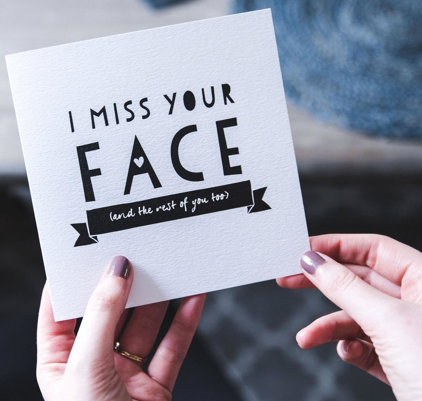 "Hands holding a white card that reads ""I miss your face (and the rest of you too)"" in black text"