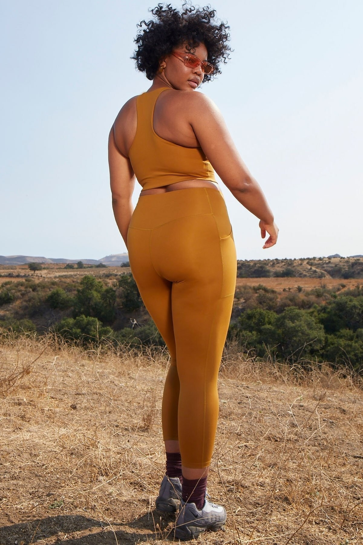 Model wears high-rise golden leggings with a matching racerback bra