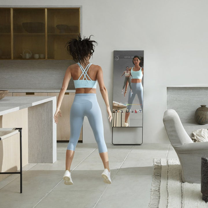 Model using The Mirror to do jumping exercises