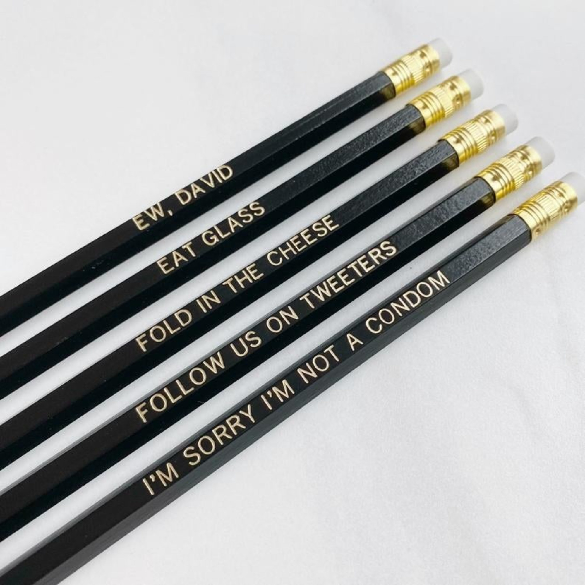 "A set of black and gold embossed pencils that read ""Ew, David,"" ""Eat glass,"" ""Fold in the cheese,"" ""Follow us on Tweeters,"" and ""I'm sorry I'm not a condom"""