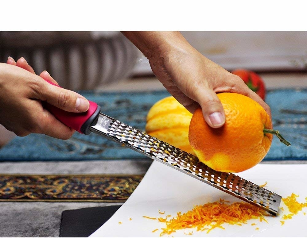 A person zesting an orange with the microplane grater.
