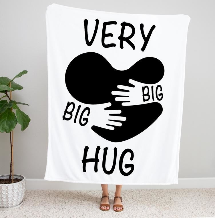 "A model holding up a blanket that reads ""Very big big hug"" with a heart motif being hugged by hands"
