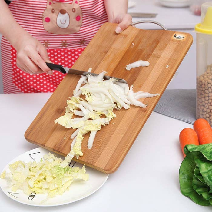 A person transferring chopped cabbage from the board to a plate.