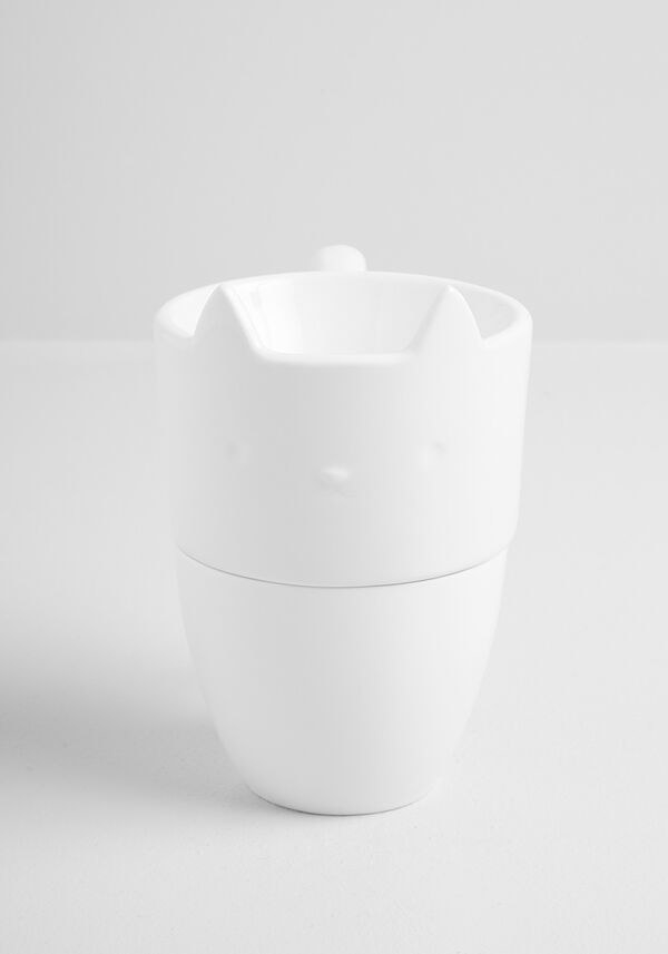 a white mug with a pour-over device on top shaped like a cat