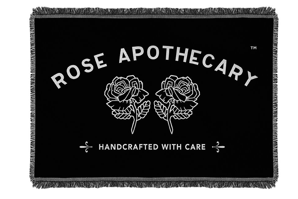 "The black fringed blanket with the Rose Apothecary logo that reads ""Rose Apothecary Handcrafted with care"""