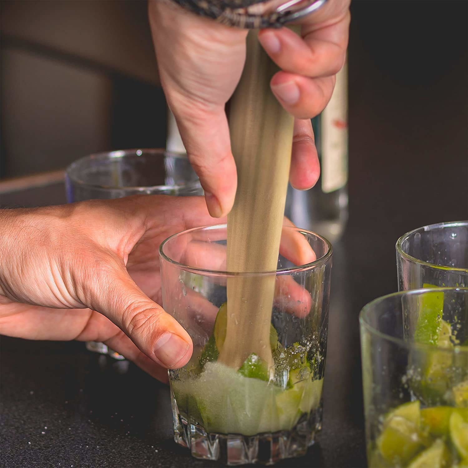 A person muddling mint, lemon, and sugar in a glass.