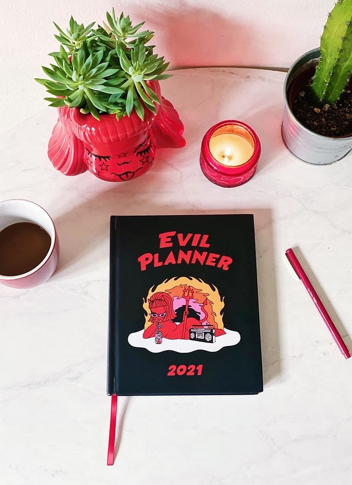 "a planner that reads ""evil planner 2021"" with an image of a little devil sipping a drink on the cover"