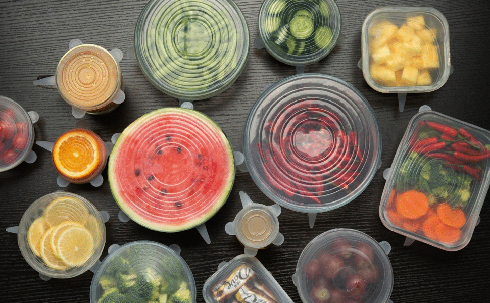 the food covers stretched across a watermelon and other fruits, vegetables, and containers of leftovers