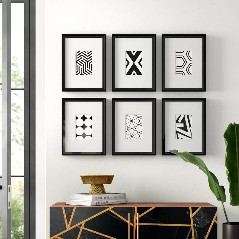 The prints hanging on a wall in two rows of three