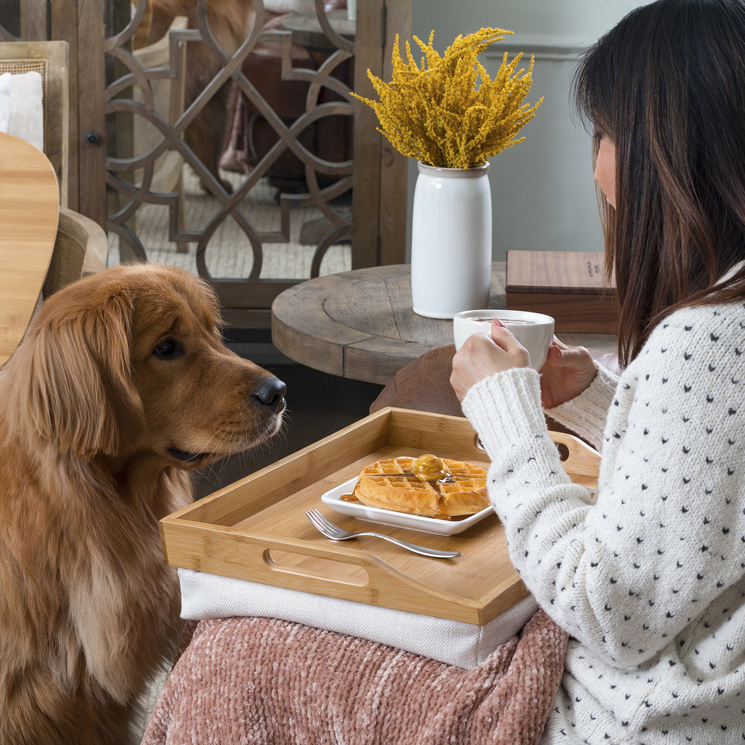 woman using the wood lap tray to eat a meal with her dog looking at her
