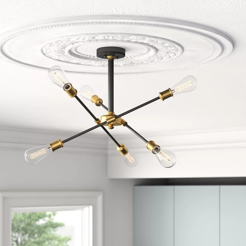 The black and gold chandelier hanging from the ceiling