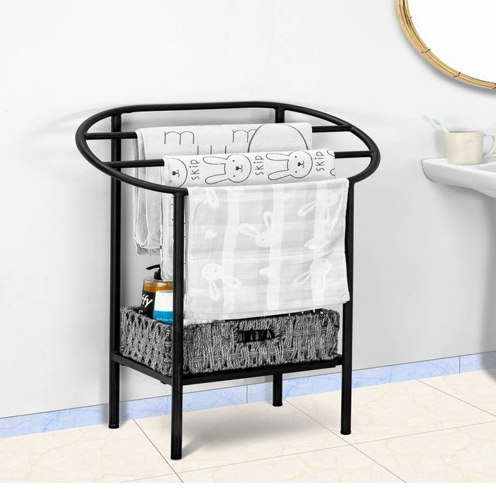 The rack, holding multiple towels to dry, as well as a box of bathroom products on the base