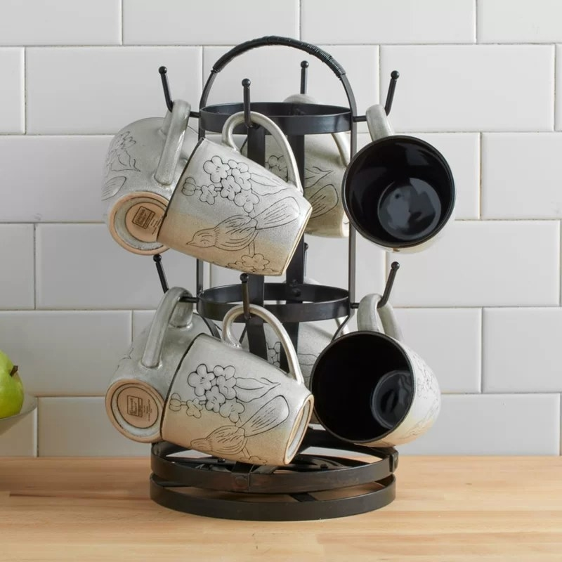The mug tree filled with mugs on a kitchen counter