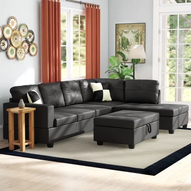 The black sectional with the matching ottoman in a living room