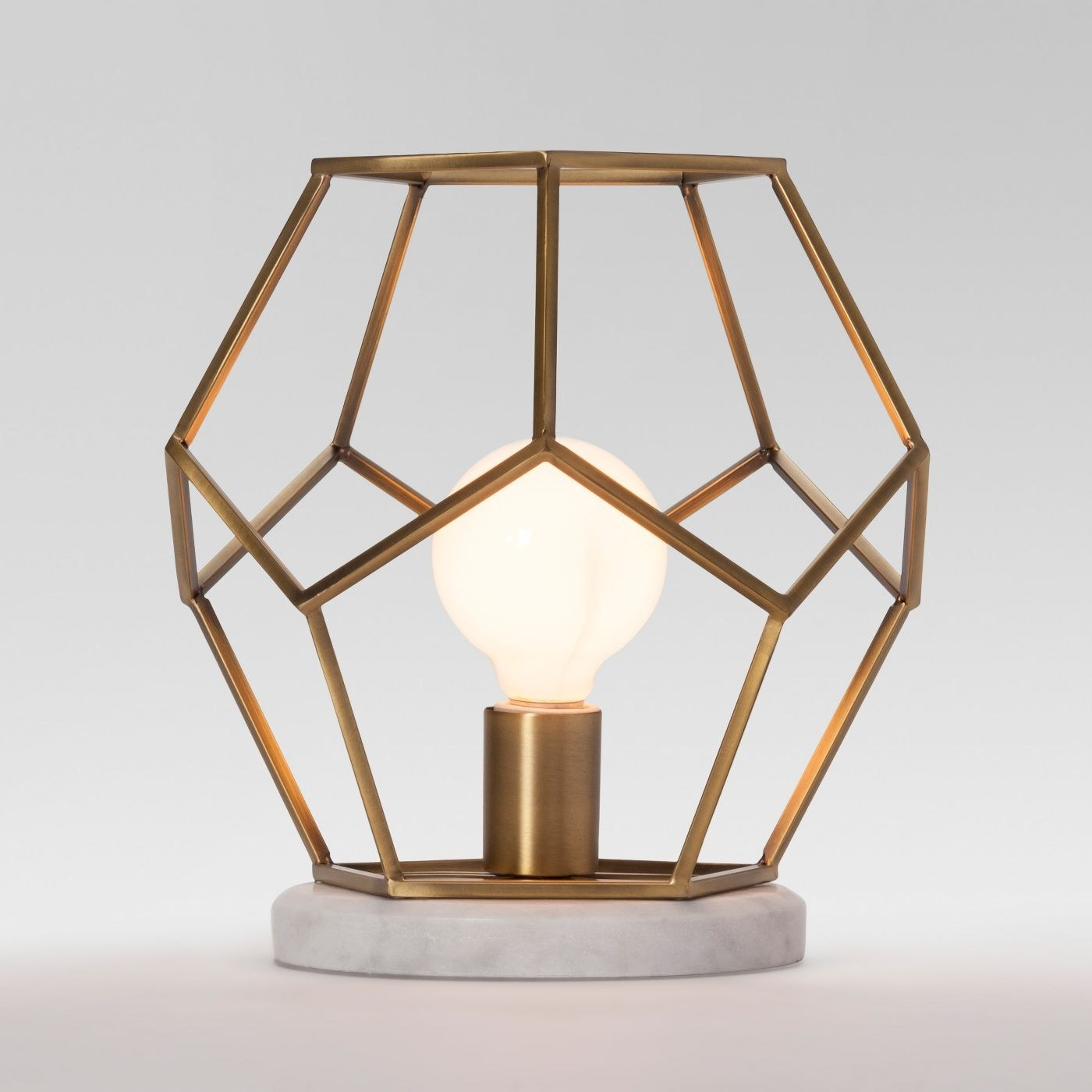 The lamp, which has a circular faux marble base, and a geometric brass-tone cage as a shade, leaving the bulb visible