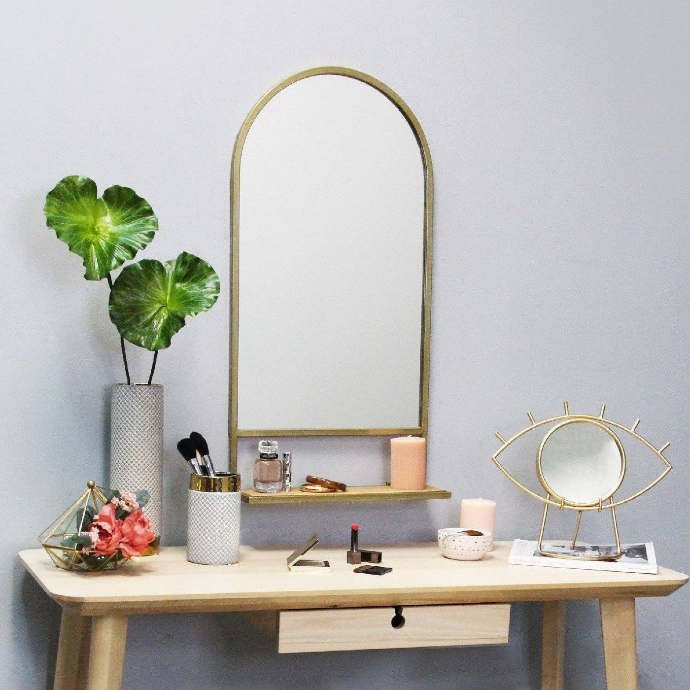 The mirror, which has a gold-toned rim, an arched top and rectangular bottom, and a collapsible shelf on the bottom