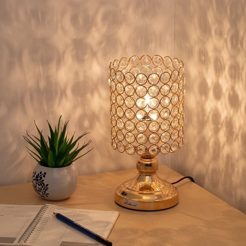 the lamp displayed on a desk with a plant, pen, and paper next to it