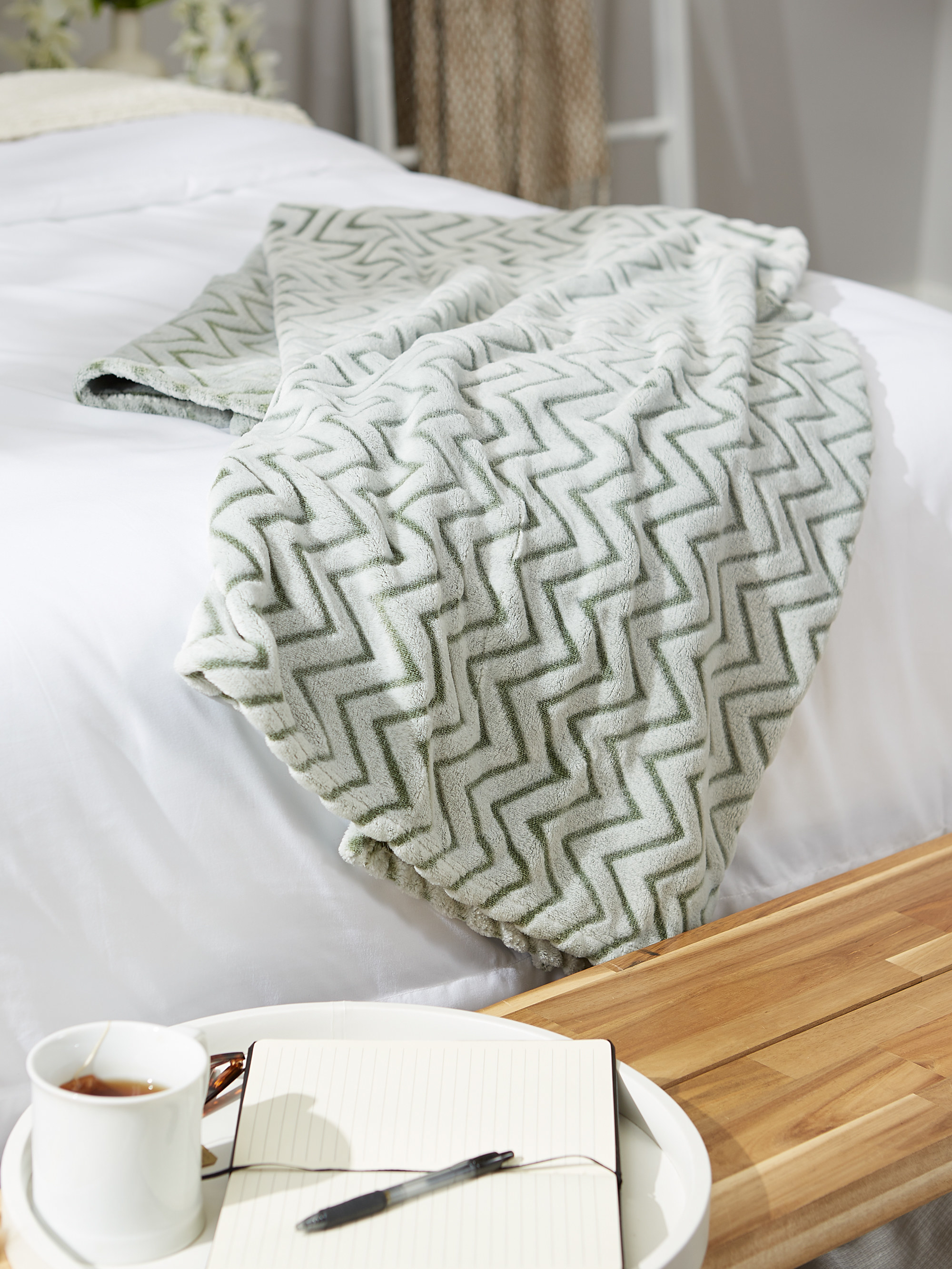 the chevron throw displayed on a bed with a tray with coffee, a pen, and a notebook on it