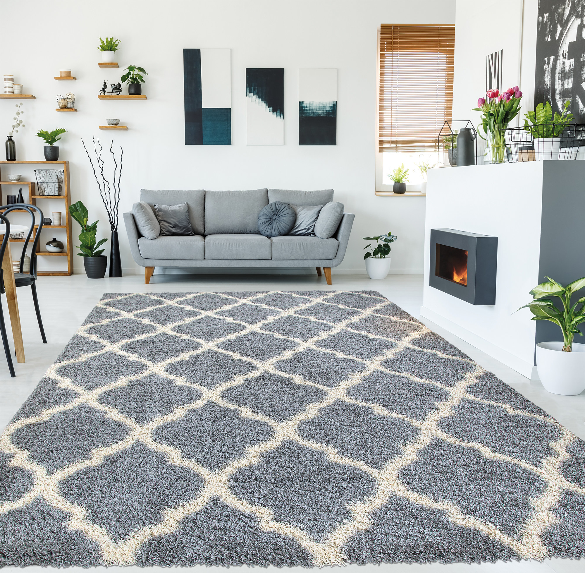 the rug displayed in a living room with a couch, plants, fireplace, and wall art surrounding it